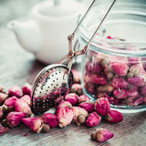 Rose buds tea, tea infuser, glass jar and teapot on background. Selective focus royalty free stock photography