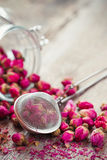 Rose buds tea, tea strainer and glass jar Stock Photos