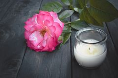 Rose and burning candle on an old wooden board. Flower frame royalty free stock photo