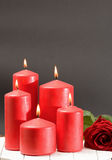 Rose , burning red candles on a table Stock Photos