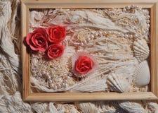 Rose, cadre en bois, perles de perle et coquilles sur le fond de fils Photographie stock