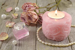 Rose candle with pink perfume. Still life of rose candle, dried flowers and pink glass bottle of perfume on wood Stock Photos