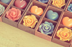 Rose candles and heart shape candles in wooden box Royalty Free Stock Images