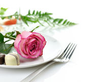 Rose and candy on a plate. Pink rose and chocolate candy on a white plate Stock Image