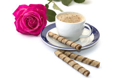 Rose and cappuccino on a saucer with a blue border Stock Image