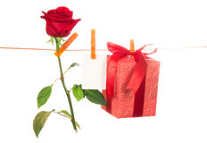 The rose, card and gift hang on a linen rope Royalty Free Stock Image