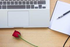 Rose, carnet, crayon et ordinateur portable de rouge sur la table en bois pour l'amour c Photographie stock libre de droits