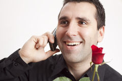 Rose, cellular and smile. Young, handsome man, arranging a date via cellphone, holding a red rose in his hand, giving a big smile Royalty Free Stock Images