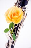 Rose On Clarinet White Background. A yellow rose mounted on a clarinet against a high key white background in the vertical format royalty free stock photo