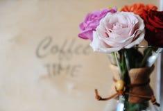 Rose colorate in una caffettiera su un fondo di legno con un tempo del caffè dell'iscrizione immagini stock