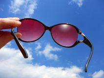 Through Rose Colored Glasses. Human hand holding a rose colored glasses. View of a blue summer sky through sunglasses royalty free stock photo