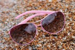 Rose colored glasses on the beach sea.  Stock Photo