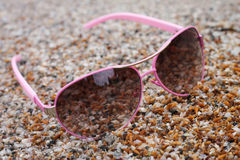 Rose colored glasses on the beach sea.  Royalty Free Stock Photography