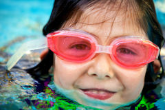 Rose Colored Goggles. A little girl in the swimming pool wearing rose colored goggles, looking straight into the camera. The water comes up to her chin and flows Royalty Free Stock Photos