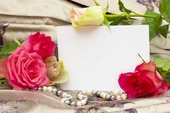 Rose con il filo delle perle e la scheda in bianco Immagini Stock