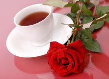 Rose with cup of tea. Red rose with cup of tea on red background royalty free stock photo