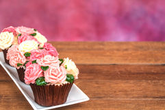 Rose cupcakes. Roses cupcake on wooden floor with multicolor background Royalty Free Stock Photos