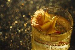 Rose dans un verre transparent et un bokeh de fond et d'or noir Photo libre de droits