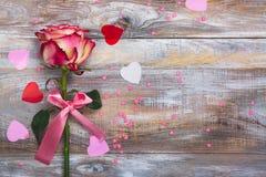 Rose de rose et de jaune avec l'arc rose et confettis décoratifs de coeurs sur le fond en bois Image libre de droits
