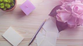 Rose de rose et une bougie rose sur un fond bleu intérieurs Le concept du romance Photos libres de droits
