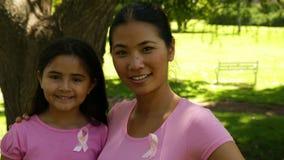 Rose de port de mère et de fille pour la conscience de cancer du sein en parc banque de vidéos
