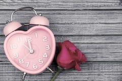 Rose de rose et montre rose de coeur sur le fond en bois bleu Image stock