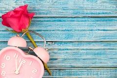 Rose de rose et montre rose de coeur sur le fond en bois bleu Image libre de droits