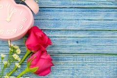 Rose de rose et montre rose de coeur sur le fond en bois bleu Images libres de droits