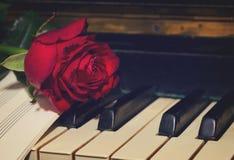 Rose de rouge avec le papier de notes sur le piano Image libre de droits