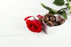 Rose de rouge, boîte de chocolats sur un fond en bois blanc Image stock