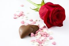 Rose de rouge, bonbon de chocolat avec la forme de coeur et sucreries Photos libres de droits