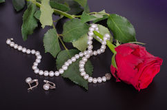 Rose de rouge, boucles d'oreille de perles et collier sur un fond noir Photographie stock