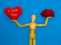 Rose de rouge, coeur et homme en bois sur le fond bleu Photo stock