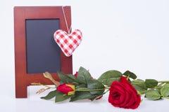 Rose de rouge, coeurs rouges et conseil d'écriture Photo stock