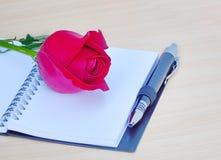 Rose de rouge d'isolement et livre sur un fond en bois Photo libre de droits