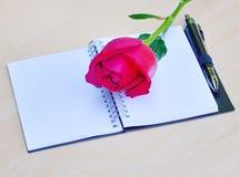 Rose de rouge d'isolement et livre sur un fond en bois Photos libres de droits