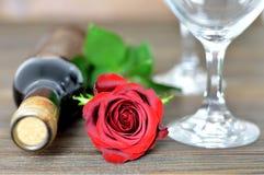 Rose de rouge, deux verres de vin et bouteille de vin rouge Photo libre de droits