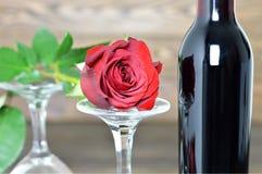 Rose de rouge, deux verres de vin et bouteille de vin rouge Image stock