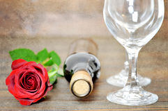 Rose de rouge, deux verres de vin et bouteille de vin sur le fond grunge Image stock
