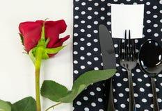 Rose de rouge et argenterie noire sur la serviette Photographie stock