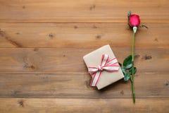Rose de rouge et boîte-cadeau de vintage sur le fond en bois de vintage Photo libre de droits