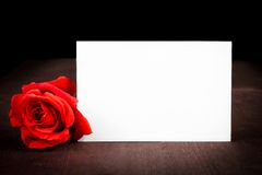 Rose de rouge et carte cadeaux vierge pour le texte sur le vieux fond en bois Photographie stock libre de droits