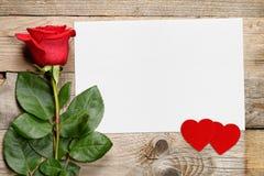 Rose de rouge et carte de voeux avec des coeurs Images stock