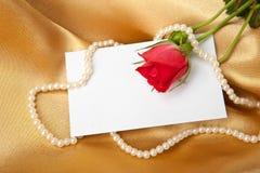 Rose de rouge et carte vierge sur le satin d'or photographie stock libre de droits