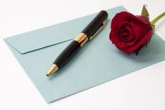 Rose de rouge et crayon noir sur l'enveloppe bleue Images libres de droits