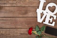 Rose de rouge et futé au-dessus du fond en bois Photos stock
