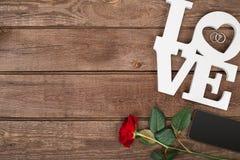 Rose de rouge et futé au-dessus du fond en bois Photographie stock libre de droits