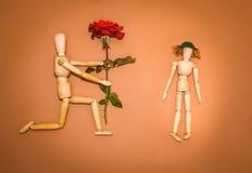 Rose de rouge et homme en bois, femme sur le fond brun Image stock