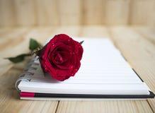 Rose de rouge et page 1 de carnet Photo stock