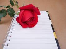 Rose de rouge et page 8 de carnet Image libre de droits